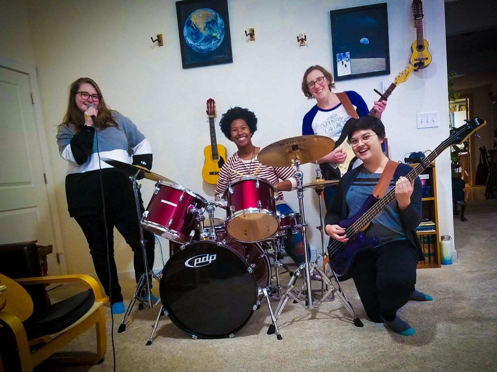 Midnight Crater: Karen Studarus (she/her, guitar), Hallie Tanner (she/her, vocals), Elisha Ewing (she/her, drums/bass), Rachel Betron (they/them, bass/drums)